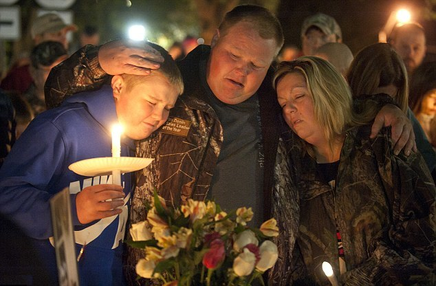 Gabriella's brother Alec, father Brian and mother Amy, comfort each other during a vigil for her on Sunda