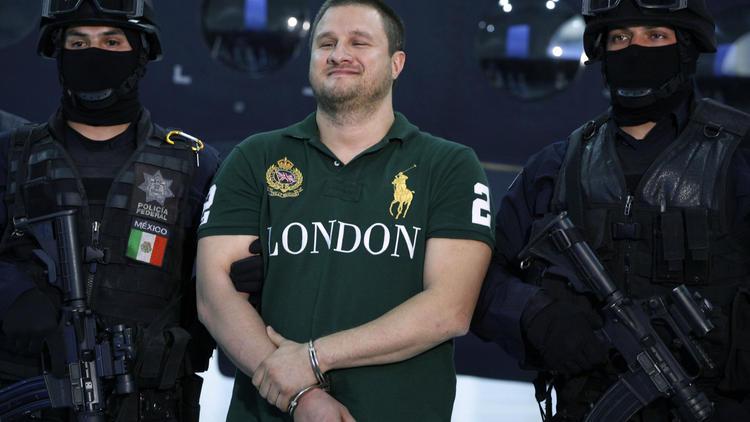 """Mexican federal police escort Texas-born suspect Edgar Valdez Villarreal, alias """"the Barbie,"""" in Mexico City in 2010."""