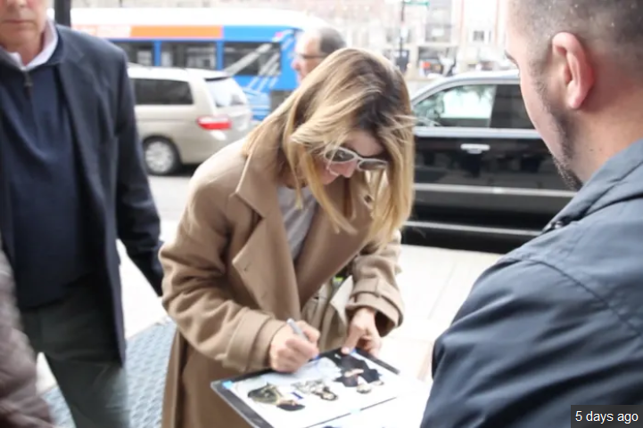 Lori Loughlin taking her case serious. Here she seen signing autographs outside her hotel.